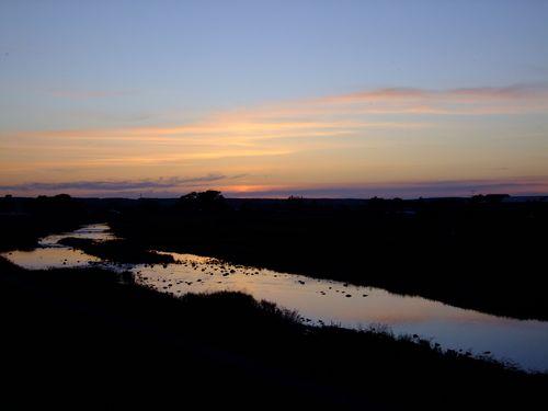 茜の空の映る川